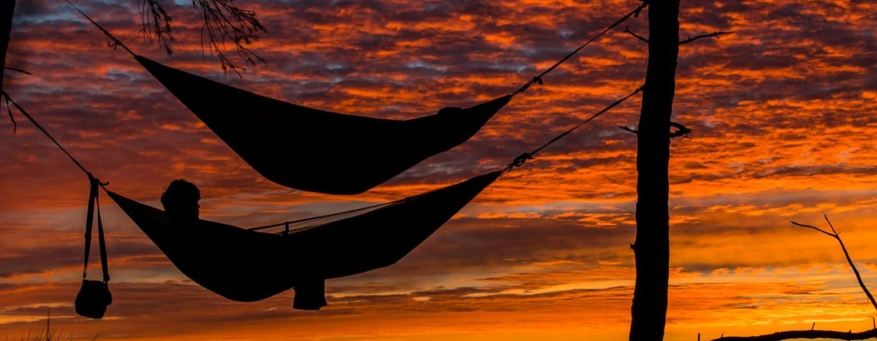 people in hammocks at dusk